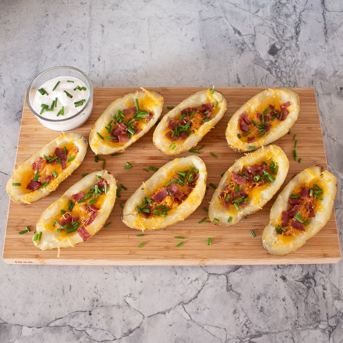 Easy recipe for loaded baked potato skins. These potato skins are topped with bacon, cheese, chives and sour cream and the perfect appetizer for any party.